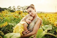 Мама и дочь в поле солнцецветов стоковая фотография