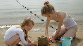 Мама и дочь играют на пляже, строя замок песка r o сток-видео