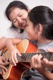 Мама и дочь играя гитару стоковое фото rf