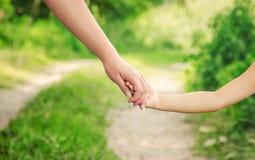 Мама и дочь идут вдоль дороги держа руки Селективный фокус Стоковое Изображение