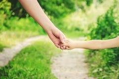 Мама и дочь идут вдоль дороги держа руки Селективный фокус Стоковая Фотография RF