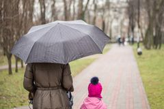 Мама и дочь идя вместе с прогулочной коляской стоковые фотографии rf