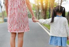 Мама и дочь конца-вверх держа руки в на открытом воздухе саде природы E стоковые изображения rf