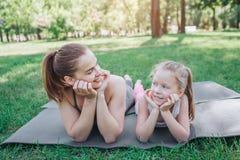 Мама и дочь лежат на carimate и смотрят один другого Они имеют некоторые остатки после разминки ` S девушки наслаждается Стоковое Фото