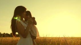 Мама и дочь околпачивают вокруг в поле со зрелой пшеницей на заходе солнца o Небольшой ребенок заполнен с акции видеоматериалы