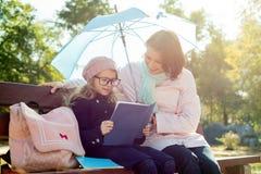 Мама и дочь отдыхают совместно на стенде в парке города стоковое изображение