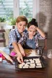Мама и дочь подготавливают печенья в кухне стоковое изображение