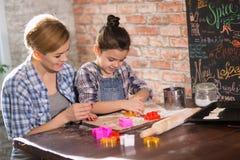 Мама и дочь подготавливают печенья в кухне стоковые изображения