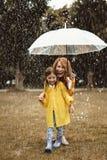 Мама и дочь пряча от дождя стоковая фотография