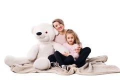 Мама и дочь сидят на одеяле и объятии стоковые фото