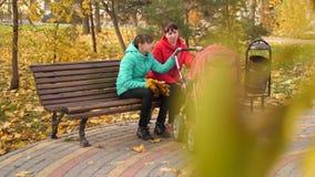 Мама и дочь сидят на стенде в парке осени и тряся прогулочной коляске с малым младенцем акции видеоматериалы