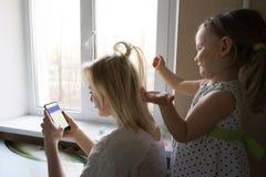 Мама и дочь сидят окном стоковые фотографии rf