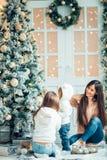 Мама и дочь украшают рождественскую елку внутри помещения Стоковое Изображение