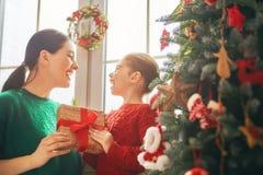 Мама и дочь украшают рождественскую елку Стоковая Фотография