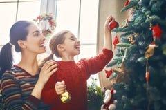 Мама и дочь украшают рождественскую елку Стоковое Изображение RF