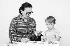 Мама и ее дом сына Мать играя игру логики с сыном Забота матери об улучшать навыки ребенка для того чтобы подготовить его в школу стоковое изображение
