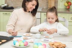 Мама и ее дочь печь совместно и украшая печенья стоковое изображение