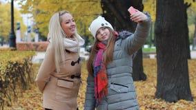 Мама и ее дочь фотографируют против фона красивого парка осени видеоматериал