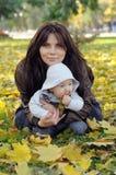 Мама и ее маленький младенец сидя на траве стоковое изображение