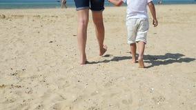 Мама и ее сын идут вдоль песочного пляжа моря, против фона моря видеоматериал
