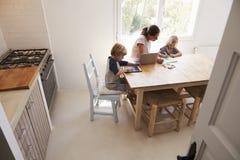 Мама и 2 дет работая на кухонном столе, повышенном взгляде Стоковое фото RF