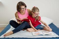 Мама и маленькая дочь прочитали книги дома в кровати Стоковая Фотография RF