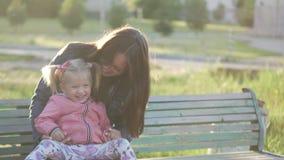 Мама и маленькая дочь сидят на скамейке в парке Весна outdoors видеоматериал