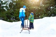 Мама и маленький сын, идут со скелетонами к холму ехать Потеха зимы на каникулы рождества семьи стоковая фотография rf
