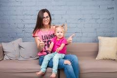 Мама и младенец играют и имеют потеху в комнате на кресле Они одеты в ярких одеждах привлекательностей стоковое изображение rf
