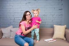 Мама и младенец играют и имеют потеху в комнате на кресле Они одеты в ярких одеждах привлекательностей стоковая фотография rf