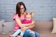 Мама и младенец играют и имеют потеху в комнате на кресле Они одеты в ярких одеждах привлекательностей стоковые изображения rf