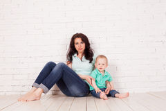 Мама и молодой сын мальчика сидят на кирпичной стене пола стоковое изображение