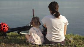 Мама и дочь выпивают зеленый коктеиль сидя на береге пруда сток-видео
