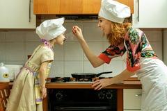 Мама и дочь в белых шляпах шеф-повара варят в кухне Стоковая Фотография RF