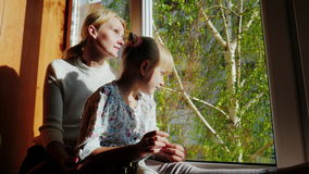 Мама и дочь 6 лет старого усаживания на windowsill, смотря вне окно Вне окна весна, зеленеет акции видеоматериалы