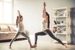 Мама и дочь делая йогу Стоковые Фотографии RF