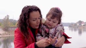 Мама и дочь играют на речном береге Маленькая девочка с ее матерью на реке играет совместно сток-видео