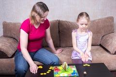 Мама и дочь играя игру таблицы Стоковое фото RF