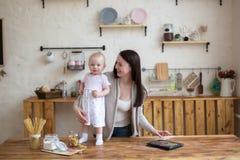 Мама и дочь имеют потеху играя вместе с таблеткой в доме i Стоковые Фото