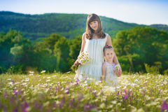 Мама и дочь на пикнике в стоцвете field 2 красивых блондинкы в стоцвете field на предпосылке лошади Стоковое Изображение