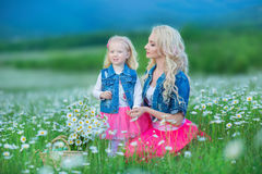 Мама и дочь на пикнике в стоцвете field 2 красивых блондинкы нося куртку джинсов и розовое gir матери и младенца юбки Стоковая Фотография RF