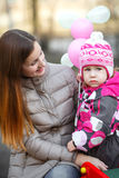Мама и дочь на скамейке в парке Стоковые Изображения RF