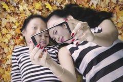Мама и дочь принимая selfie с осенью листьев Стоковое Фото