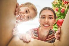 Мама и дочь раскрывая подарок на рождество Стоковое Изображение RF