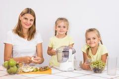 Мама и дочь сидят на таблице и режут плодоовощ для juicing Стоковые Изображения