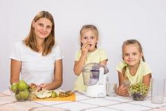 Мама и дочь сидят на таблице с juicer и плодоовощ Стоковые Изображения
