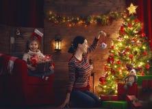 Мама и дочь украшают рождественскую елку Стоковая Фотография RF
