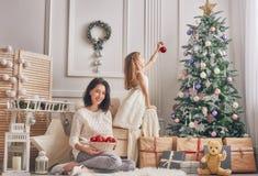 Мама и дочь украшают рождественскую елку Стоковые Фото