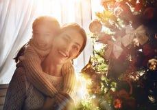 Мама и дочь украшают рождественскую елку Стоковые Изображения
