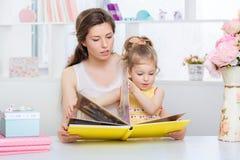 Мама и дочь читая совместно Стоковые Изображения RF